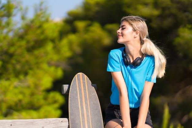 側にいる屋外でスケートを持つティーンエイジャーの女の子