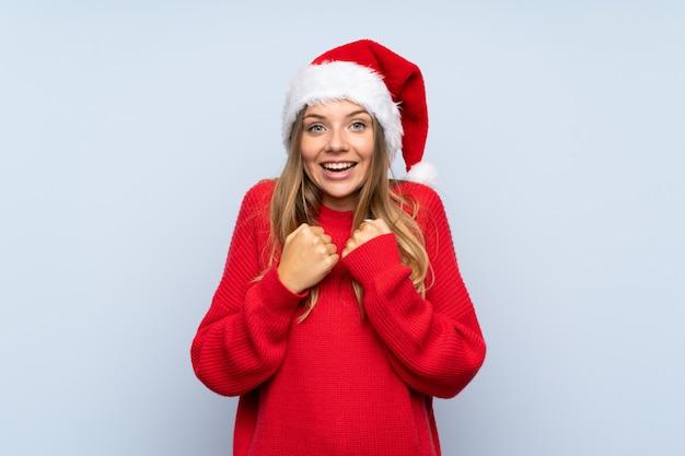 勝利を祝う分離の青い壁の上のクリスマス帽子の少女