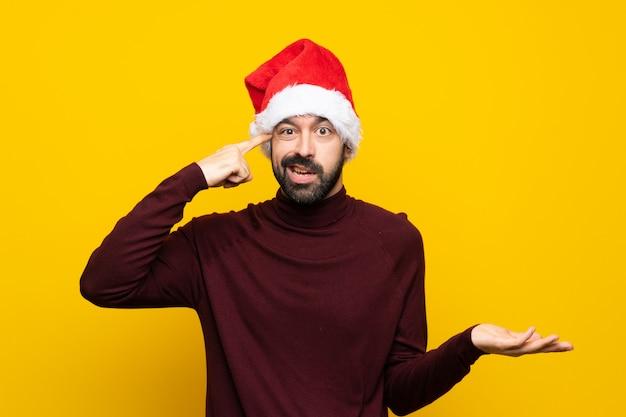 Человек с рождественской шляпой над изолированной желтой стеной делает жест безумия, кладя палец на голову