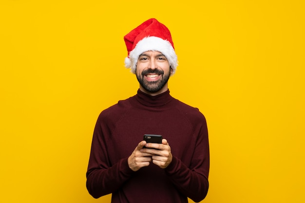 携帯電話でメッセージを送信する孤立した黄色の壁の上のクリスマス帽子の男