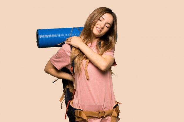 孤立した黄色の壁に努力したための肩の痛みに苦しんでいる若いバックパッカー女性