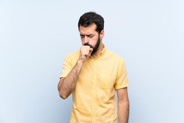 孤立した青い壁の上のひげを持つ若い男は咳と気分が悪いで苦しんでいます。