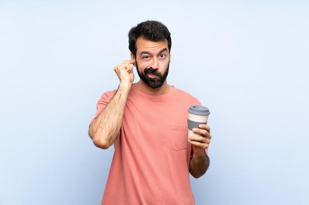 イライラして耳を覆う分離の青い壁にコーヒーを持ち帰ってひげを保持している若い男