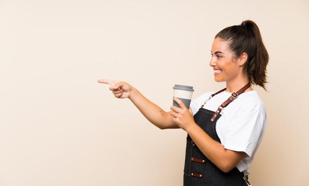 Молодой работник женщина, держащая прочь кофе, указывая в сторону, чтобы представить продукт