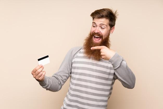 クレジットカードを保持している孤立した背景に長いひげを持つ赤毛の男