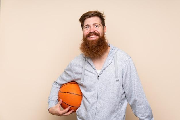 バスケットボールのボールで孤立した背景の上の長いひげを持つ赤毛の男