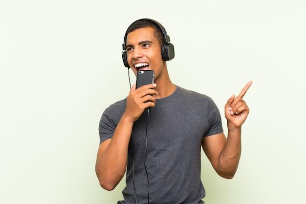 孤立した緑の壁を越えて携帯電話で音楽を聴く若いハンサムな男