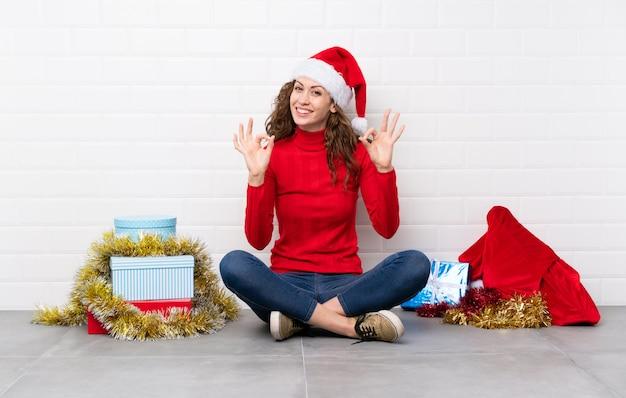 Девушка в рождественские праздники, сидя на полу, показывая знак ок с пальцами