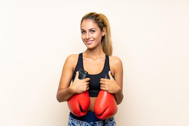 孤立した壁の上のボクシンググローブを持つ若いスポーツ女性