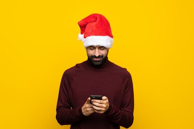 携帯電話でメッセージを送信する分離の黄色の壁の上のクリスマス帽子の男