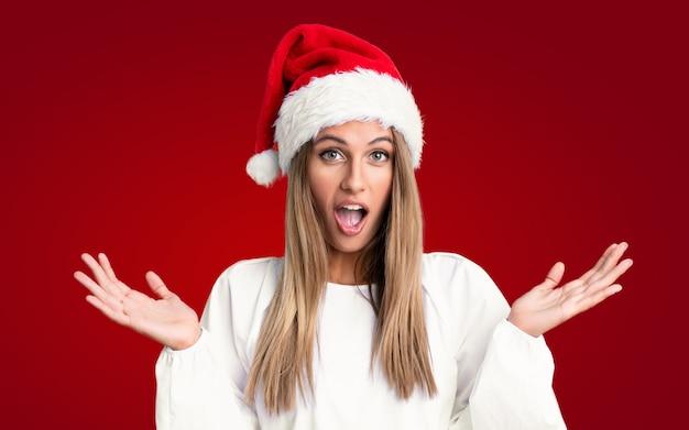 驚きの表情で孤立した壁の上のクリスマス帽子の少女