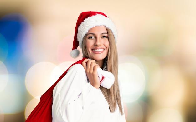 Молодая белокурая женщина, собирающая сумку, полную подарков в рождественские каникулы на несосредоточенной стене