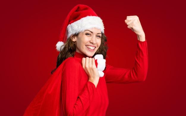 Девушка с шляпой рождества держа сумку рождества полную подарков над изолированной красной стеной