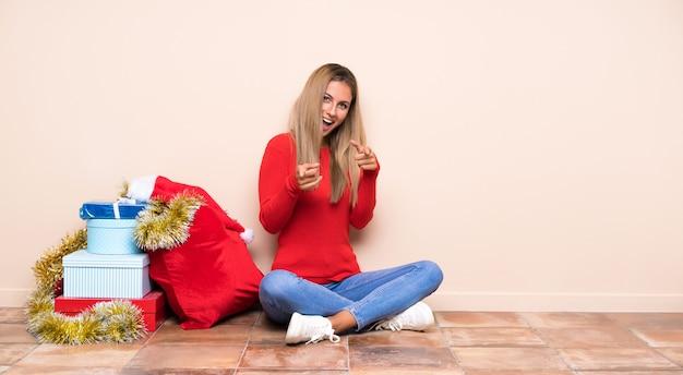 Девушка в рождественские праздники, сидя на полу указывает пальцем на вас
