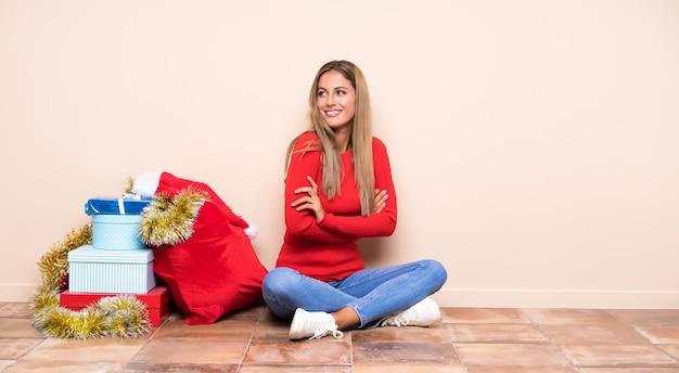 Девушка в рождественские праздники сидит на полу от смеха