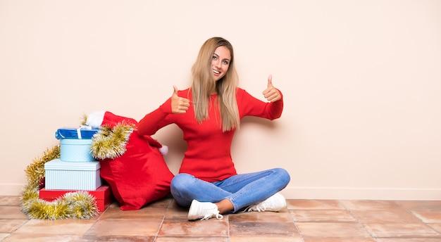 Девушка в рождественские праздники, сидя на полу, давая недурно жест