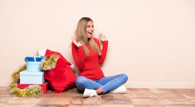 Девушка в рождественские праздники, сидя на полу с удивлением выражение лица