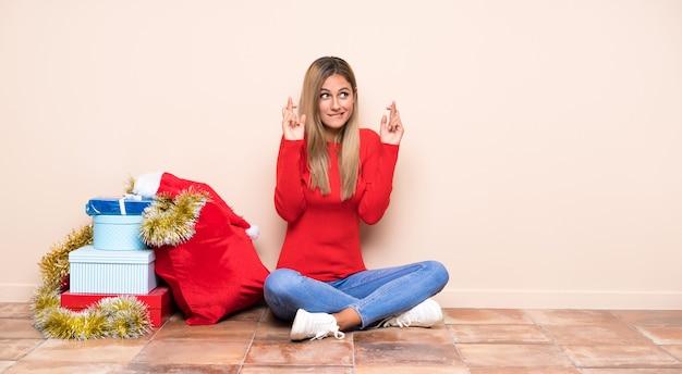 Девушка в рождественские праздники, сидя на полу с скрестив пальцы