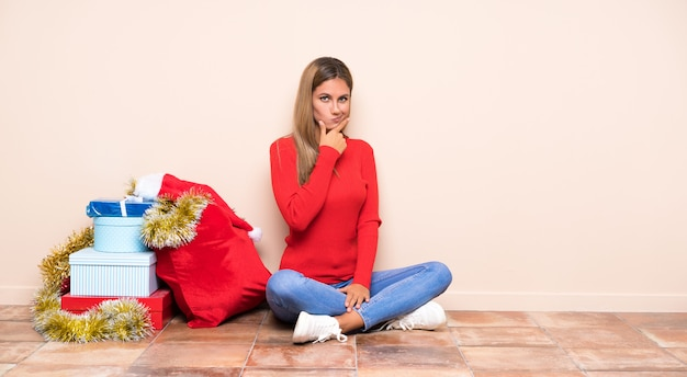 Девушка в рождественские праздники, сидя на полу, думая, идея