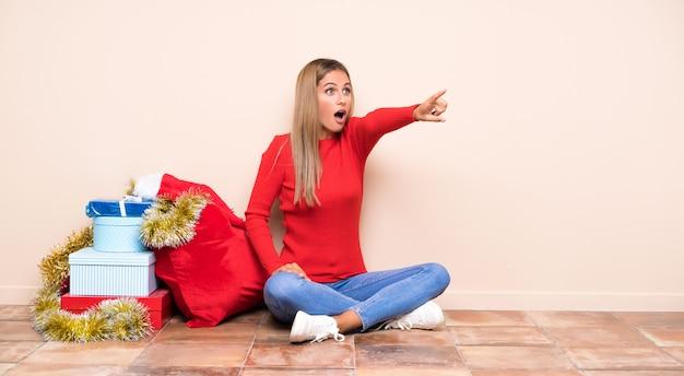 Девушка в рождественские праздники, сидя на полу, указывая