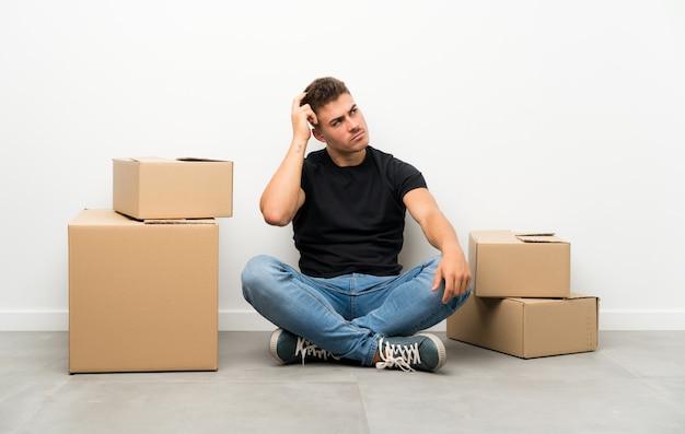 ハンサムな若い男の疑問を持つボックス間で混乱している表情で新しい家に移動