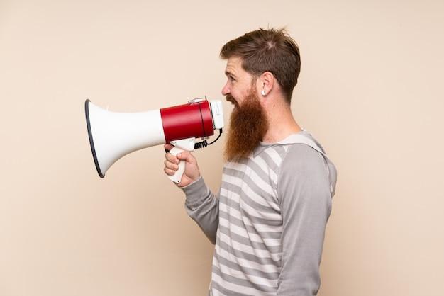 メガホンを通して叫んで孤立した壁の上の長いひげを持つ赤毛の男