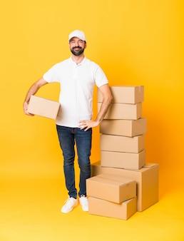 Полная длина доставщик среди коробок на изолированной желтой стене позирует с руки на бедре и улыбается