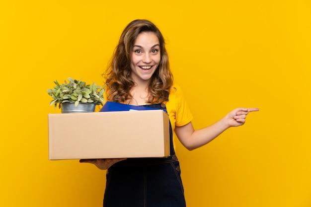 驚きと側に指を指しているの完全な箱を拾いながら移動を行う若いブロンドの女の子