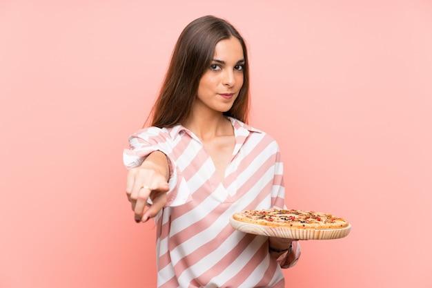 孤立したピンクの壁にピザをかざす若い女性が自信を持って表情で指を指す
