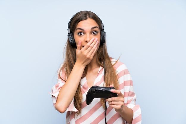 驚きの表情で分離された青い壁を越えてビデオゲームコントローラーで遊ぶ若い女性