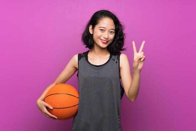 Молодая азиатская женщина играя баскетбол над изолированной фиолетовой стеной