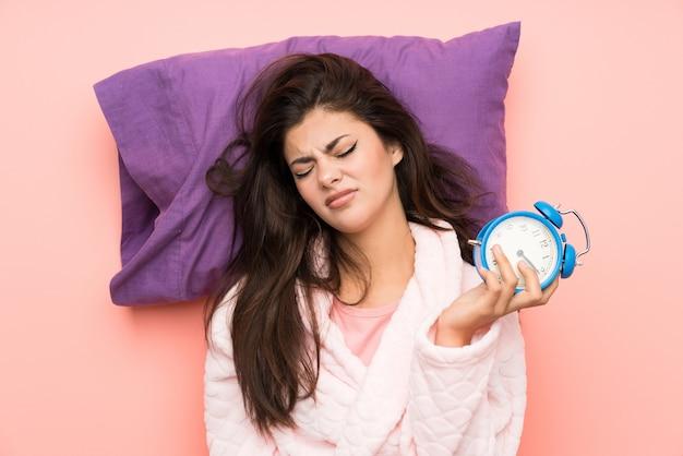 Девушка-подросток в халате на розовом фоне и подчеркнуто держит винтажные часы