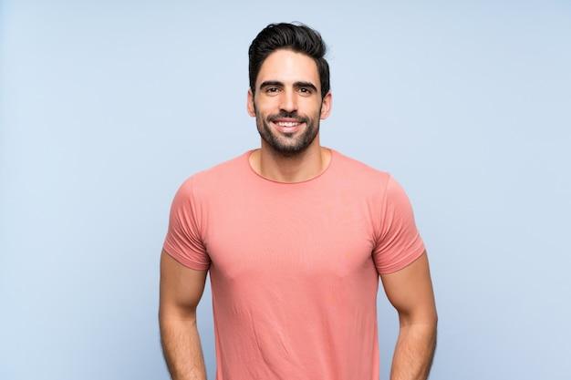 孤立した青い壁の笑いにピンクのシャツでハンサムな若い男
