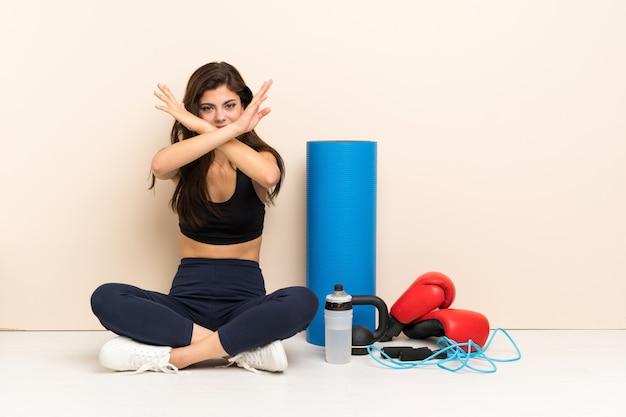 Подросток спортивная девушка сидит на полу, не делая жест