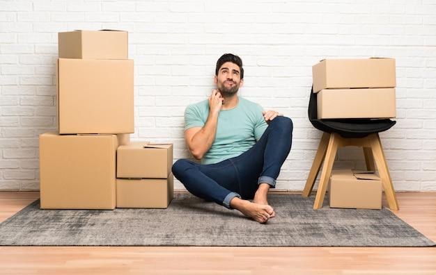 アイデアを考えてボックス間で新しい家に移動するハンサムな若い男