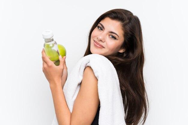 リンゴと水のボトルと分離の白い壁の上のティーンエイジャーのスポーツ少女