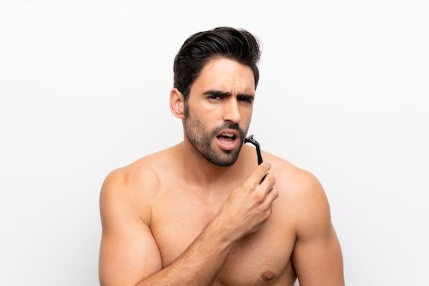 Человек бреет бороду над изолированной белой стеной