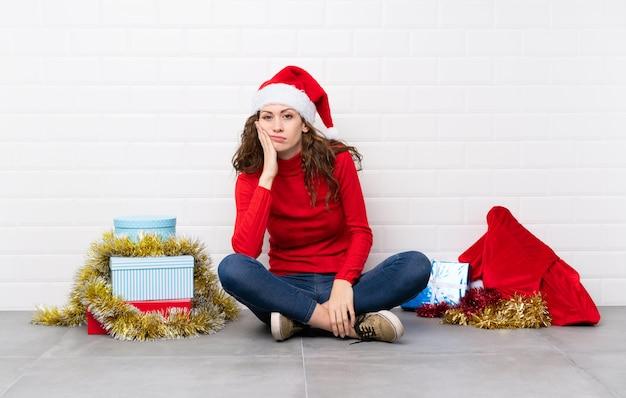 不幸で不満の床に座ってクリスマス休暇の女の子