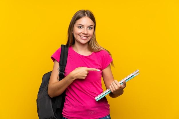 Молодая девушка студента над изолированной желтой стеной и указывать его