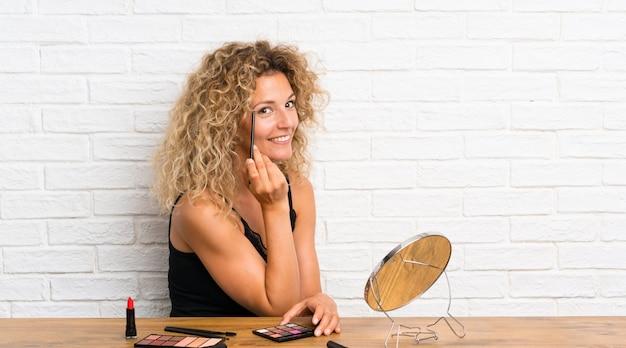 多くのテーブルで化粧ブラシを持つ若い女性