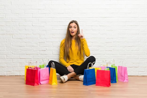 指を上向きのアイデアを考えて買い物袋の多くを持つ若い女の子