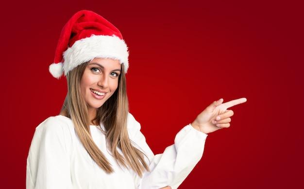 Девушка с шляпой рождества над изолированной стеной указывая палец в сторону
