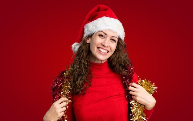 孤立した赤い壁の上のクリスマス帽子の少女