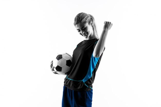 Белокурая девушка подростка футболиста над изолированной белой стеной