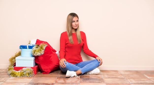 Девушка в рождественские праздники, сидя на полу, стоя и глядя в сторону
