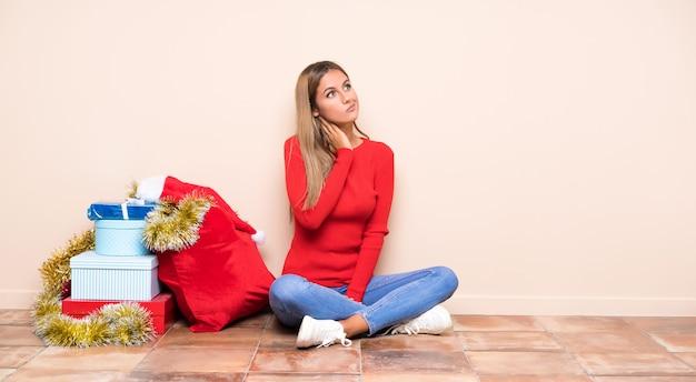 アイデアを考えて床に座ってクリスマス休暇の女の子