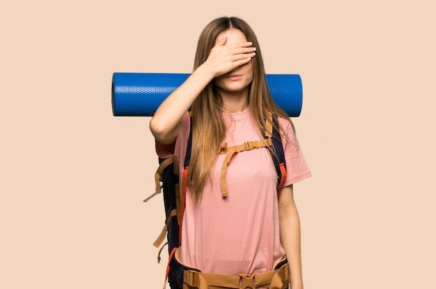 手で目を覆っている若いバックパッカーの女性。何かを見たくない