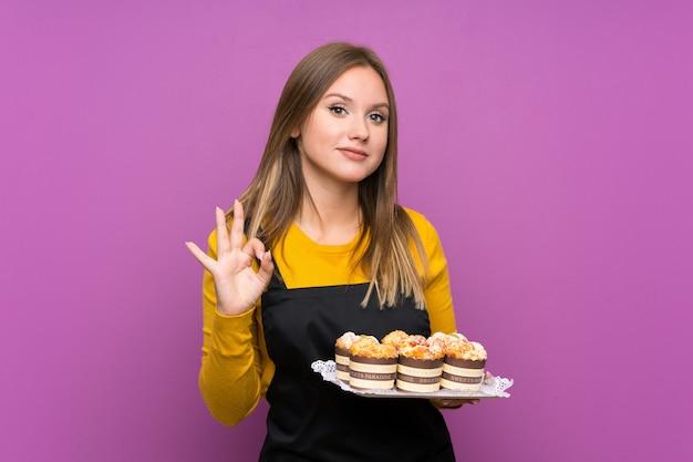 Девочка-подросток держит много разных мини-пирожных