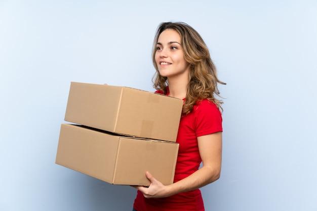 別のサイトに移動するボックスを保持している若いブロンドの女性