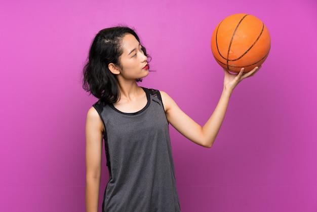孤立した紫色の背景にバスケットボールをプレーする若いアジア女性